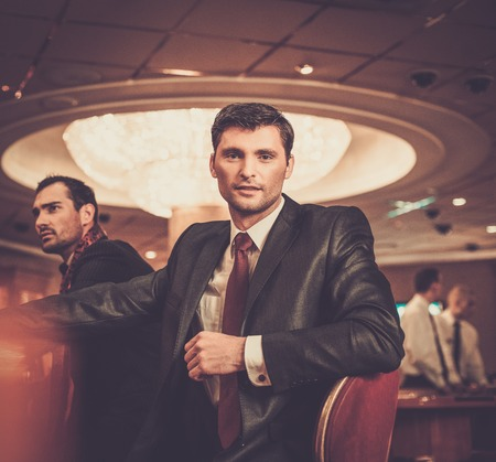 Two fashionable men in suits behind table in a casino photo