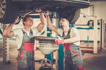 Deux mécaniciens de changer l'huile dans un atelier de voiture