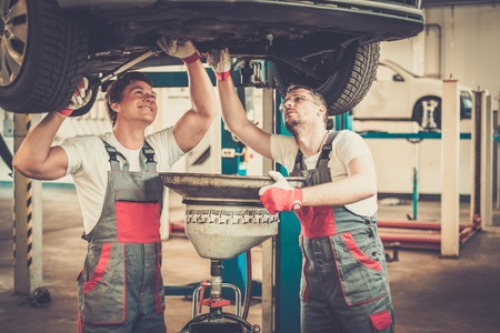 mechanical parts: Two mechanics changing oil  in a car workshop