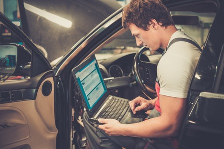 serviceman: Serviceman making car diagnostics with laptop in a workshop Stock Photo