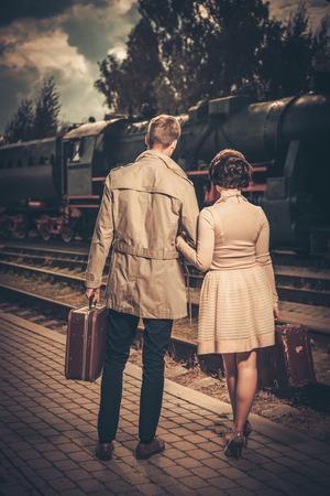 treno espresso: Coppie di stile vintage con valigie su piattaforma stazione ferroviaria
