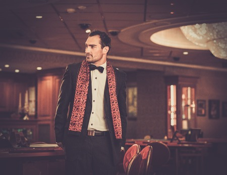 Handsome man wearing suit in luxury casino interior photo