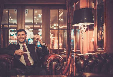 caras emociones: Hombre sonriente hermoso que se sienta con una taza de café en un interior de lujo