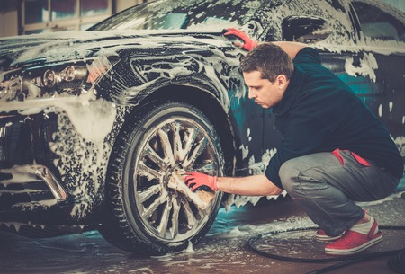 lavar: Llantas de aleación Hombre trabajador de lavado del coche en un túnel de lavado