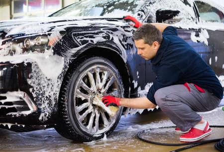 lavarse las manos: Llantas de aleaci�n Hombre trabajador de lavado del coche en un t�nel de lavado