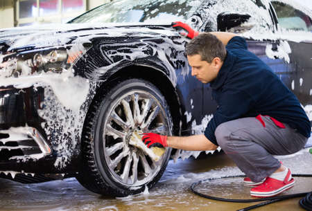 car in garage: Man worker washing cars alloy wheels on a car wash