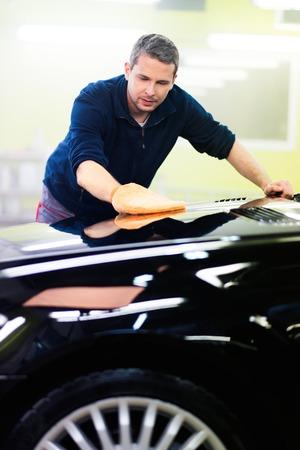car body: Man worker polishing car on a car wash