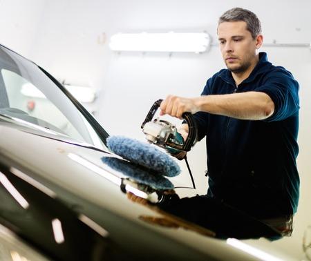 O homem em um carro lavagem de carro polimento com uma m
