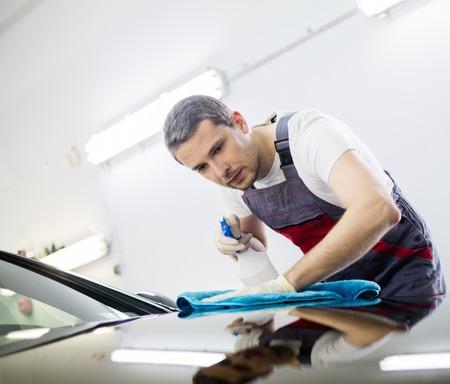 autolavaggio: Operaio su una macchina di lavaggio auto pulizia con uno spray