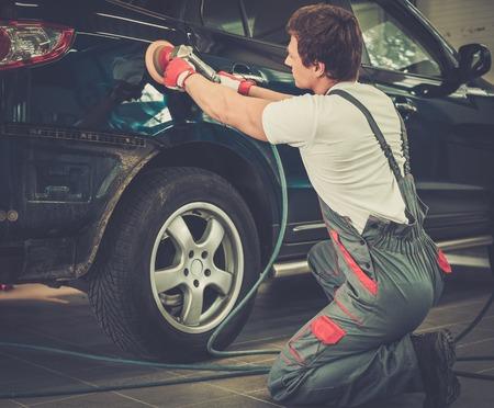 body paint: Serviceman pulido carrocer�a del coche con la m�quina en un taller Foto de archivo
