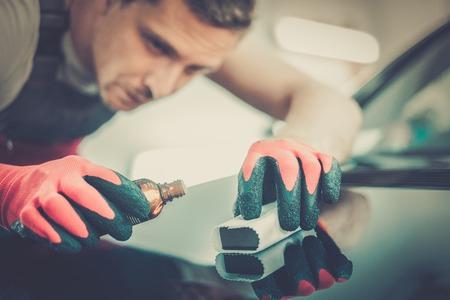 garage automobile: Ouvrier sur un lavage de voiture appliquant revêtement nano sur un capot