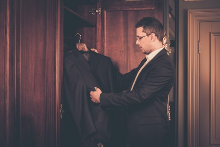 Middle-aged man taking suit from wardrobe photo