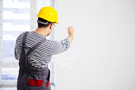 Foreman with construction plan in new building interior photo