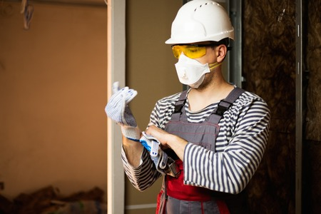 safety googles: Builder in protective wear during new building construction Stock Photo