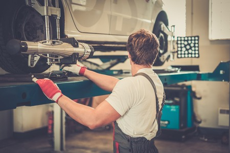 car shop: Young serviceman checking wheel alignment  in a car workshop Stock Photo