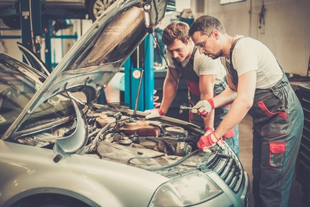 oil change: Two mechanics fixing car in a workshop