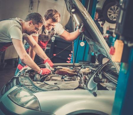 fixing: Two mechanics fixing car in a workshop