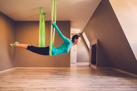 girl on swing: Young woman performing antigravity yoga exercise