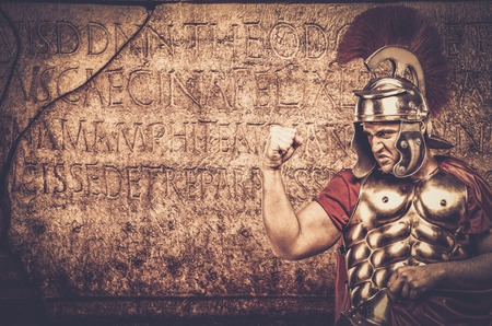 roman soldier: Roman legionary soldier in front of  wall with ancient writing
