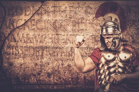 cascos romanos: Soldado legionario romano delante de la pared con la escritura antigua