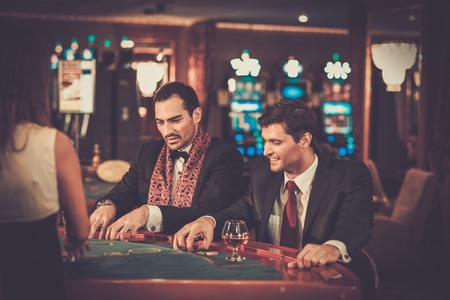 fichas de casino: Dos hombres de moda en trajes de detr�s de la mesa en un casino Foto de archivo