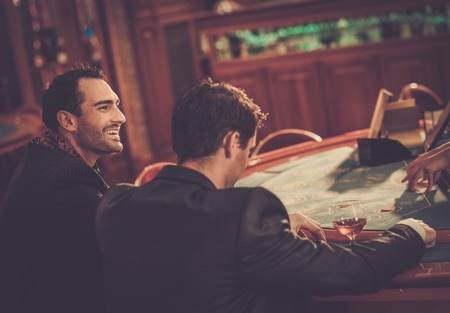 casino tokens: Two fashionable men in suits behind table in a casino Stock Photo