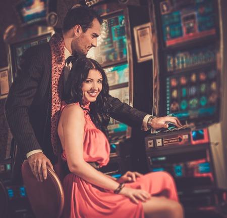 Hermosa pareja cerca de la máquina tragaperras en un casino
