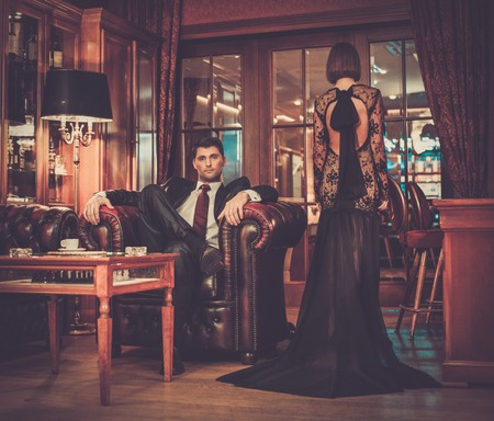 Elegant couple in formal dress in luxury cabinet interior photo