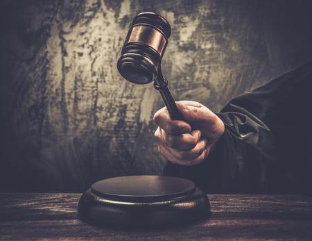 martillo juez: La mano del juez sostiene el martillo de madera
