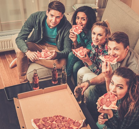 people eating: Grupo de amigos multi�tnicas con la pizza y botellas de bebidas que tiene partido