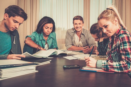 final: Multi ethnic group of students preparing for exams in home interior behind table Stock Photo