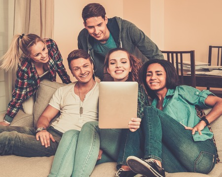 group shot: Group of young friends taking selfie in home interior