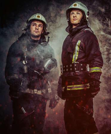 bombero: Dos bomberos con el casco y el hacha en una cortina de humo Foto de archivo