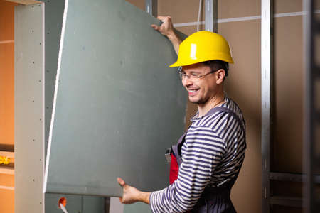 plasterboard: Builder with plasterboard in new building interior Stock Photo