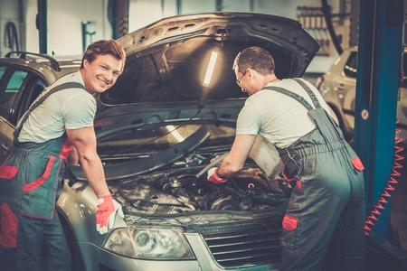 car repair shop: Two mechanics fixing car in a workshop