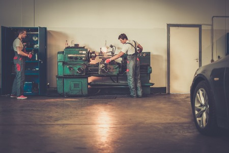 car workshop: Serviceman working on turning lathe in car workshop Stock Photo