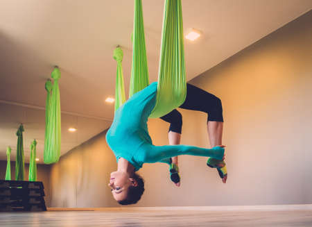 aerial: Young woman performing antigravity yoga exercise
