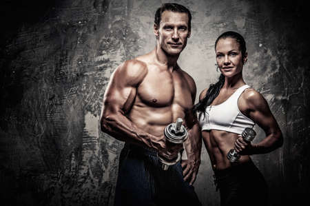 powerlifting: Athletic man and woman with a dumbbells