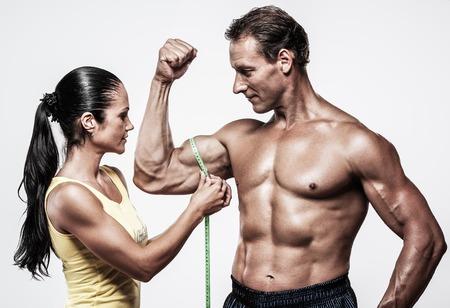 woman measuring: Woman measuring athletics man biceps