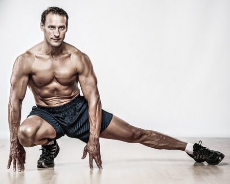man legs: Handsome muscular man doing stretching exercise