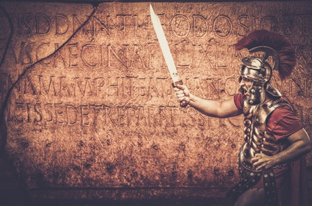 legionary: Roman legionary soldier in front of  wall with ancient writing
