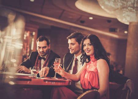 donna ricca: La gente dietro tavolo da poker in un casinò
