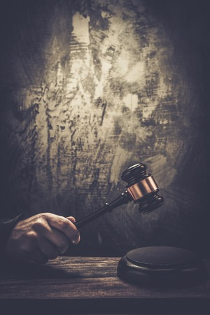 verdicts: Judges hand holding wooden hammer Stock Photo