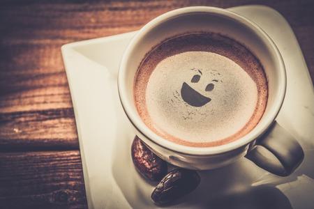 cara sonriente: Taza de caf� en una mesa de madera con smiley en �l
