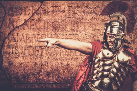 praetorian: Roman legionary soldier in front of  wall with ancient writing
