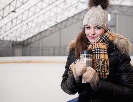 sports hall: Girl with mug of hot drink on ice skating rink