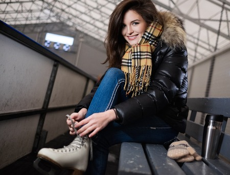 iceskates: Cheerful girl putting on skates  on ice skating rink Stock Photo