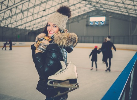 iceskates: Cheerful girl with skates on ice skating rink Stock Photo