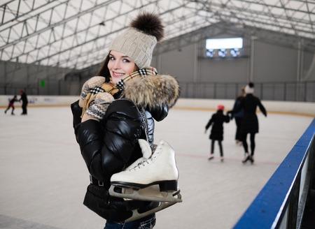 patinando: La muchacha alegre con los patines en la pista de patinaje sobre hielo Foto de archivo