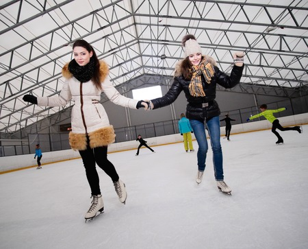 iceskates: Two girls on ice-skating rink